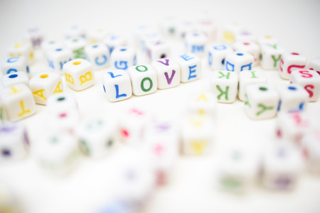 Word liefde samengesteld uit kleurrijke kralen kubussen met brieven verspreid rond, op wit Stockfoto