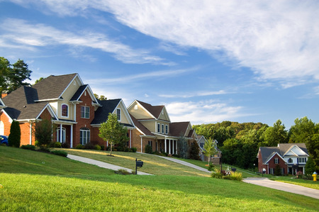 suburb: Brick houses in America. There are two-story houses with red brink and colored siding. There are green lawns in front of the houses, and driveways are visible. Some lawns have small trees, and there are many larger trees in the background. The blue sky an