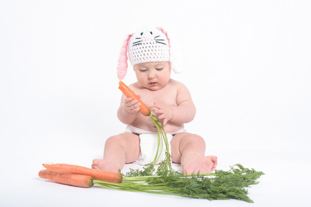nibbling: Baby in a costume of rabbit nibbling carrot, isolated on white