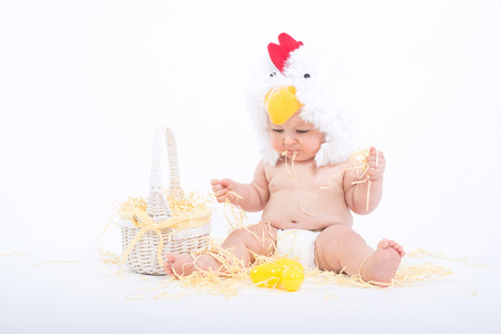 Baby in a costume of rooster sitting in a scattered hay munching straw, isolated on white 版權商用圖片