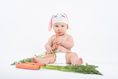 distrust: Baby boy in rabbit hat holding fresh carrot, looking with distrust