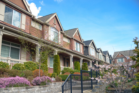 American street with townhouses with nice landscaping under blue sky Standard-Bild