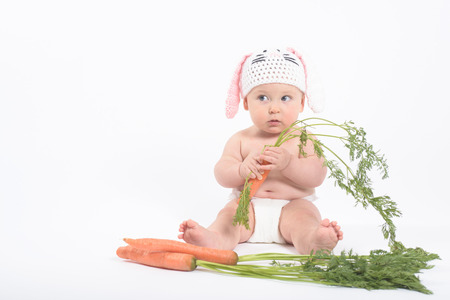distrust: Baby boy in rabbit hat holding fresh carrot looking with distrust, on white background