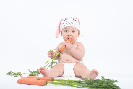 eyes wide: Chubby baby in rabbit hat with mouth and eyes wide open biting fresh carrot, on white background