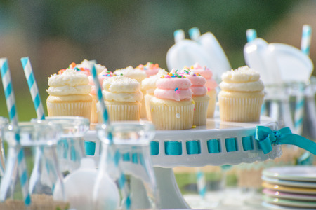 a jar stand: Baby birthday decoration in blue with bottles of milk and cupcakes Stock Photo