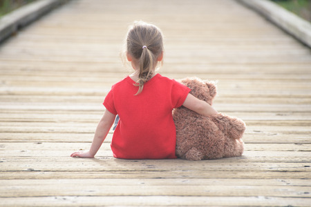 hug: Little girl in a red dress waiting on a boardwalk hugging teddybear, view from behind