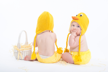 Two babies in chicken costumes with white basket, view from behind photo