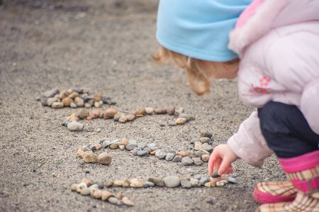 Little girl on the winter beach composing numbers from small rocks