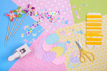 spinner: Colorful accessories for craft, scissors, paper, ribbon, punch, egg shapes, view from above