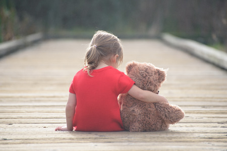ni�os tristes: Secretos de la infancia son los m�s compartidos con amigo confiable. Y si usted es peque�o oso de peluche ni�a triste est� dispuesto a ser su amigo perfecto. Foto de archivo