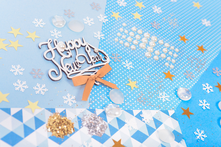 card making: Bright and shiny accessories on colorful paper for Christmas and New Year card making and scrapbooking Stock Photo