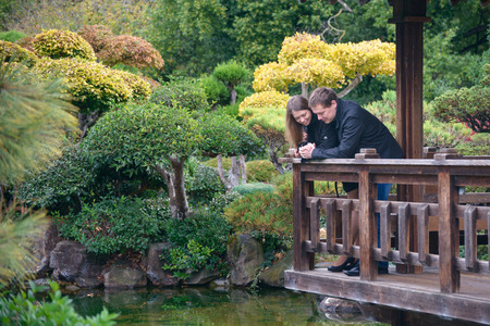Young romantic couple - good-looking man and attractive woman - standing on the bridge in beautiful Japanese garden, talking, holding hands and looking on the water. Stock Photo