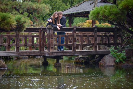 Young romantic couple - good-looking man and attractive elegant woman - standing on the bridge in beautiful Japanese garden, talking, hugging and looking on the water.