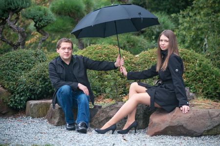 Young romantic couple with umbrella in park