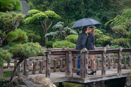 Young romantic couple with umbrella on bridge