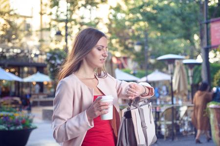 vestidos de epoca: Young pretty woman checking time hurrying down city street