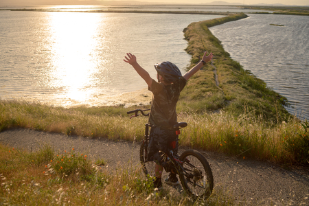 Happy boy with open arms riding his bike at sunset Banco de Imagens