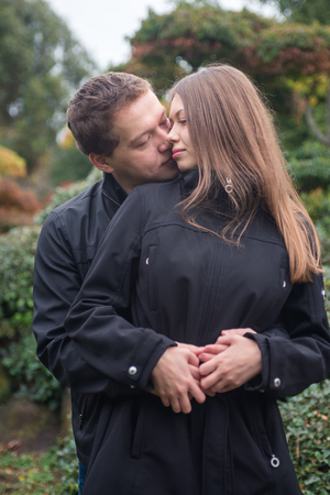 Young romantic couple hugging and kissing outside