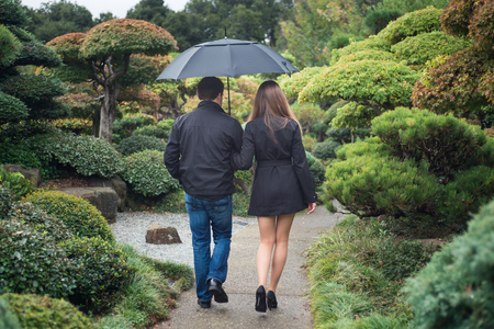 Young romantic couple walking together in park with umbrella Stock Photo