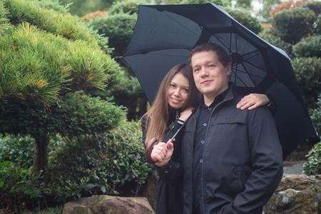 Young romantic couple hugging under umbrella outside
