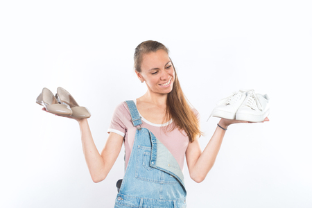 Woman holding two pairs of shoes