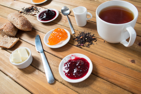 Crispy rolls with butter, apple jam and hot tea for breakfast