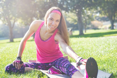 Young attractive woman working out in summer park