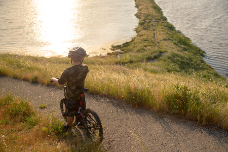 Boy in helmet riding his mountain bike at sunset