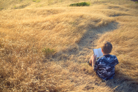 Boy reading book outside at sunset Stock Photo