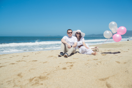 Young romantic couple sitting on the beach with balloons Imagens