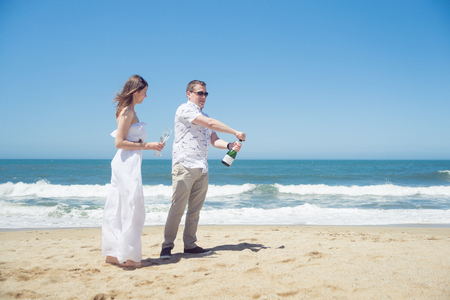 Happy couple on the beach with champagne