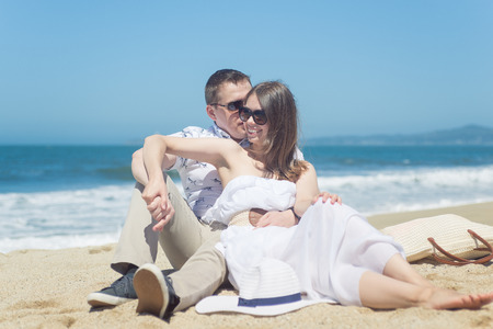 average guy: Young romantic couple sitting on the beach