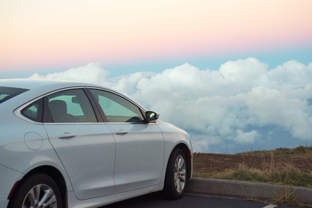 White car in mountains above the clouds at sunset or sunrise