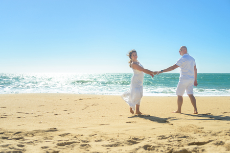 average guy: Young romantic couple walking on the beach holding hands Stock Photo