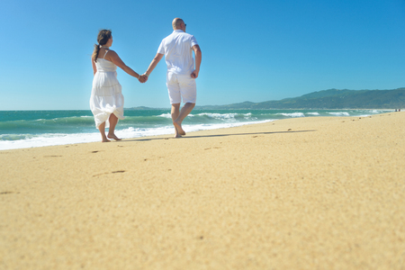 Young romantic couple walking on the beach holding hands 免版税图像