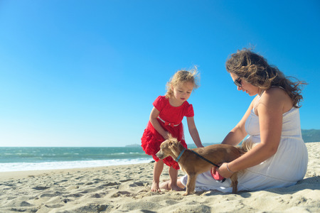 Mother and daughter in red dress and dog on the beach Banco de Imagens