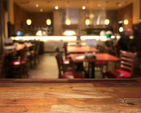 Empty wooden table top with blurred restaurant on background