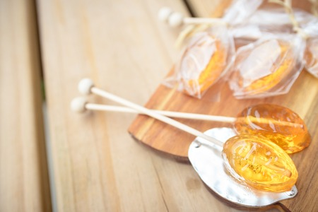 Honey caramel candy lollipop on wooden background