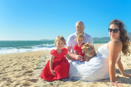 Family with sisters in red dress and dog on the beach