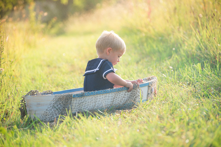 Boy in vintage sailor suit in boat on grass