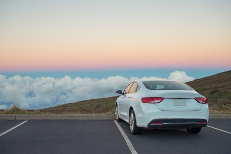 Witte auto in bergen boven de wolken bij zonsondergang of zonsopgang