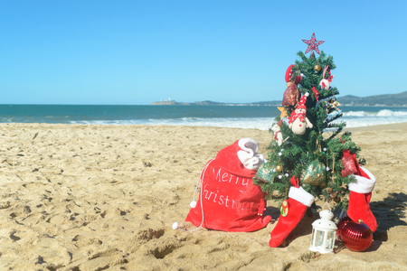 christmas tree and red santa bag of presents at the beach stock photo 91587645 - Christmas At The Beach