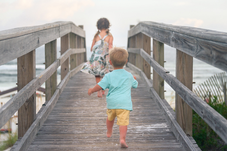 Boy and girl running on wooden deck on the beach