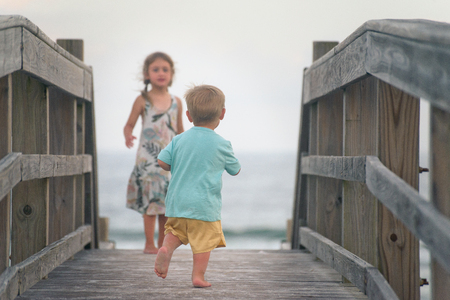 Boy and girl running on wooden boardwalk on the beach