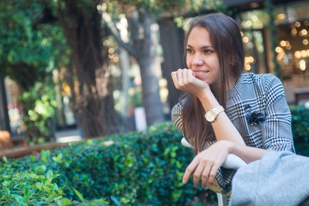 Smiling happy woman with wrist watch in the city Foto de archivo