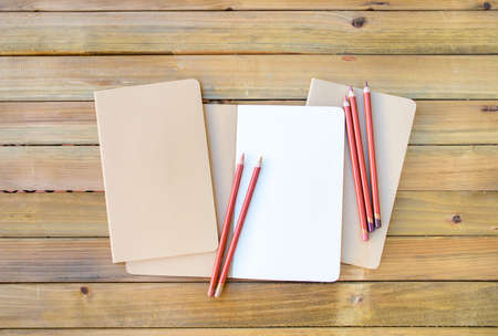 Notepad mockup with blank paper and pencils on wooden background 스톡 콘텐츠