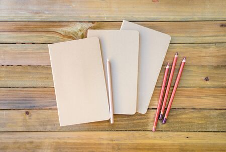 Notepad mockup with blank cover and pencils on wooden background 스톡 콘텐츠