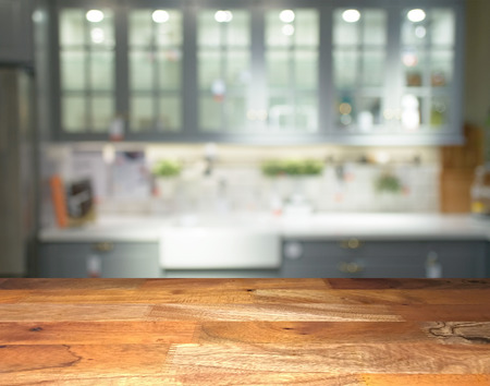 Empty wooden display table top front with blurred kitchen on background