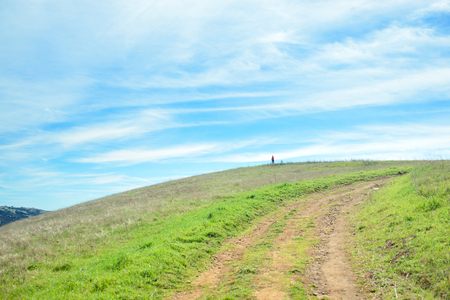 Trail in rural landscape with hiker on top of the hill, green grass hills under cloudy sky