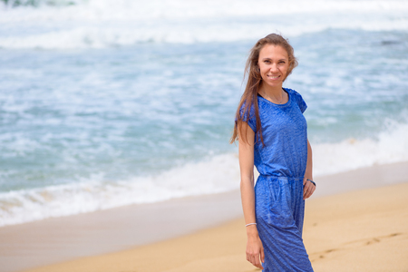 Beautiful smiling young girl in blue walking on the beach on vacation
